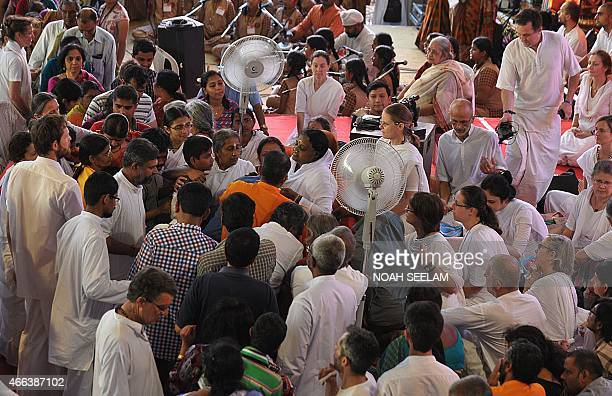 Indian spiritual figure Mata Amritanandamayi known by her followers as amma hugs a devotee as others look on during an event in Hyderabad on March 15...