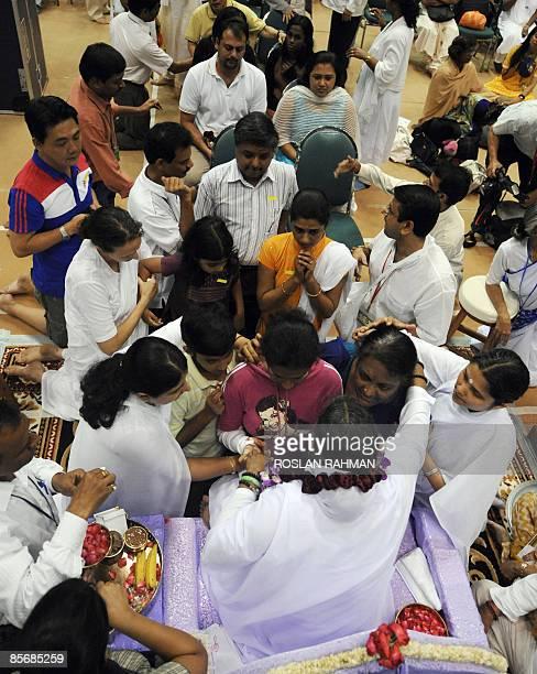 Indian spiritual leader Mata Amritanandamayi better known worldwide as 'Hugging Saint' hugs people in Singapore on March 29 2009 Mata Amritanandamayi...