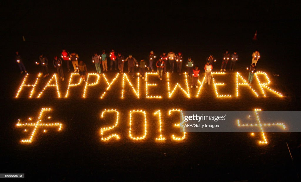 Indian sportsmen of Madan mohan malviya stadium, light candles to welcome the New Year in Allahabad on December 31, 2012. Sydney kicked off a wave of dazzling firework displays welcoming in 2013, from Dubai to Moscow and London, with long-isolated Yangon joining the global pyrotechnics for the first time. AFP PHOTO/ Sanjay KANOJIA