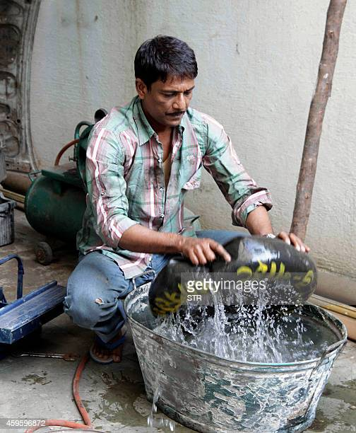 Indian stage television and film actor Adil Hussain repairs a tyre puncture during the promotion of the upcoming Hindi Film 'Zed Plus' directed by...