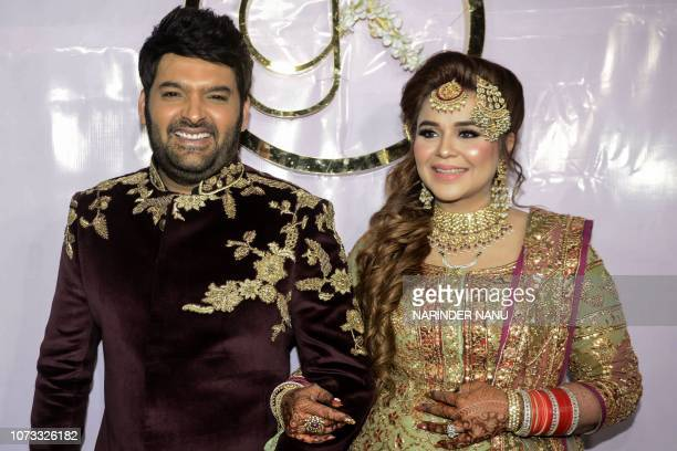 Indian standup comedian and producer Kapil Sharma and his wife Ginni Chatrath pose during their wedding reception party at a hotel in Amritsar on...