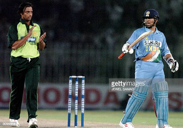 Indian star batsman Sachin Tendulkar is congratulated by Pakistani speed star Shoaib Akhtar after completing his century during the second One Day...