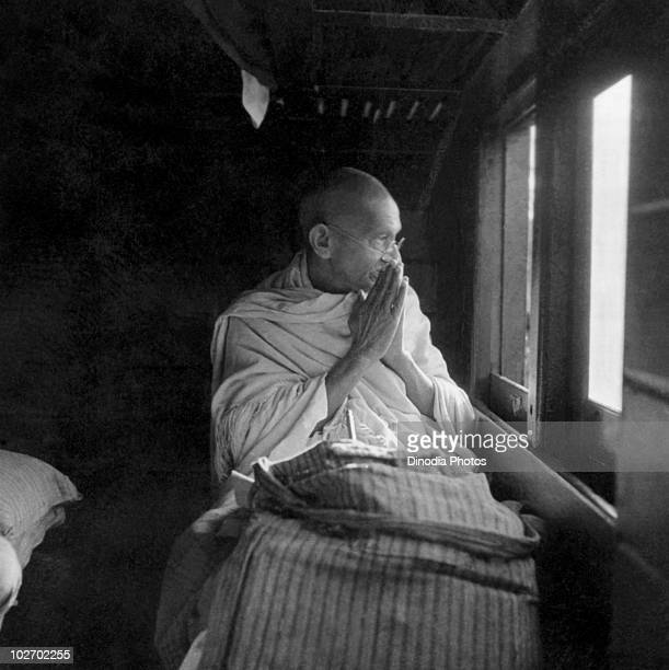 Indian statesman and activist Mohandas Karamchand Gandhi greets people through the window of a train 1940