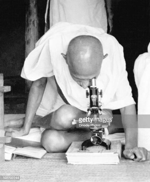Indian statesman and activist Mohandas Karamchand Gandhi observes leprosy bacteria through a microscope at Sevagram Ashram circa 1942