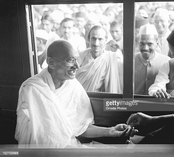 Indian statesman and activist Mohandas Karamchand Gandhi receives a donation in a train compartment 1940 Acharya Kripalani and Radhakrishna Bajaj are...