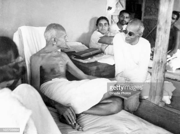 Indian statesman and activist Mohandas Karamchand Gandhi talking with Chakraborty Rajagopalachari in his hut at Sevagram Ashram 1942