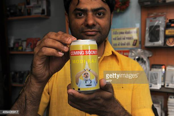 Indian storeholder Mittal Soni poses with a 'Coming Soon Modi Raj' FM Radio and music player made from tin cans at his shop in Ahmedabad on December...