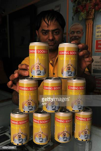 Indian storeholder Mittal Soni poses with 'Coming Soon Modi Raj' FM Radios and music players made from tin cans at his shop in Ahmedabad on December...