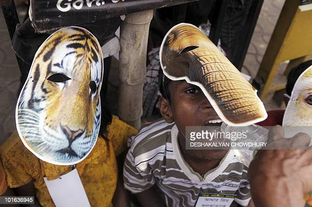 Indian street children wearing tiger and elephant masks drink water while they prepare to take part in an Environment Day awareness rally in Kolkata...