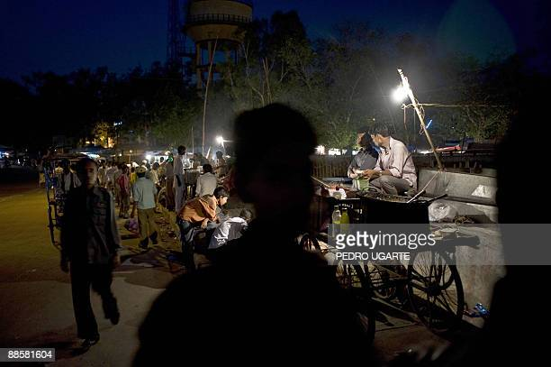 Indian street sellers wait for costumers at night in a street of New Delhi on June 19, 2009. India's annual inflation rate slipped into negative...