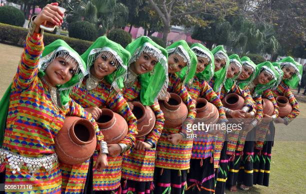 Indian student members of a folk dance group take a selfie photograph with a mobile phone at Punjabi University in Patiala on February 11 2016 India...