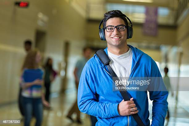 Indian student wearing headphones while walking to class in hallway