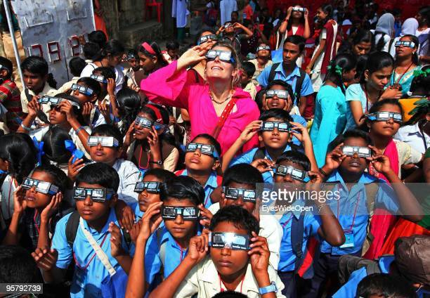 Indian students and a tourist woman observe the rare Annular Solar Eclipse on January 15 2010 at the central stadium of Thiruvananthapuram in Kerala...