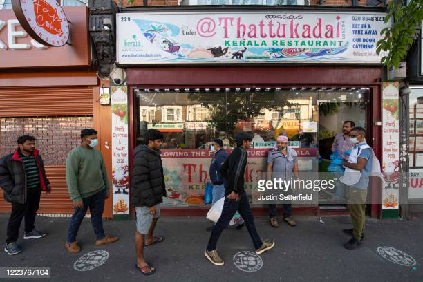 Indian students and members of the Indian community queue for free food parcels at a local restaurant prepared by the Malayalee Association of the...