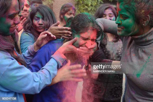 Indian students celebrate the Holi festival with coloured powder at Guru Nanak Dev University in Amritsar on February 28 2018 Holi the popular Hindu...