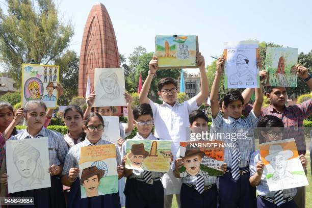 Indian students display paintings of the Flame of Liberty memorial and Indian freedom fighter Shaheed Bhagat Singh during the 99th anniversary of the...