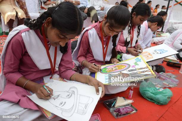 Indian students draw paintings of the Indian freedom fighter Shaheed Bhagat Singh during the 99th anniversary of the Jallianwala Bagh massacre in...