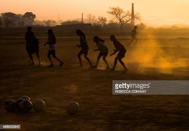 Indian students from 'The Talented Girls' and 'The Superstars' Yuwa School football training teams take part in a practice session at a football...