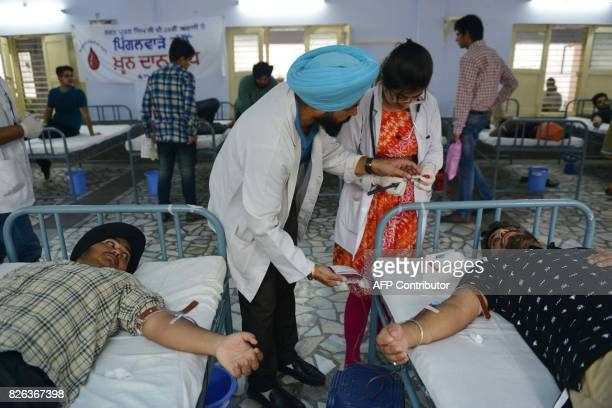 Indian students give blood during a blood donation camp to mark the 25th anniversary of the death of humanist and philanthropist Bhagat Puran Singh...