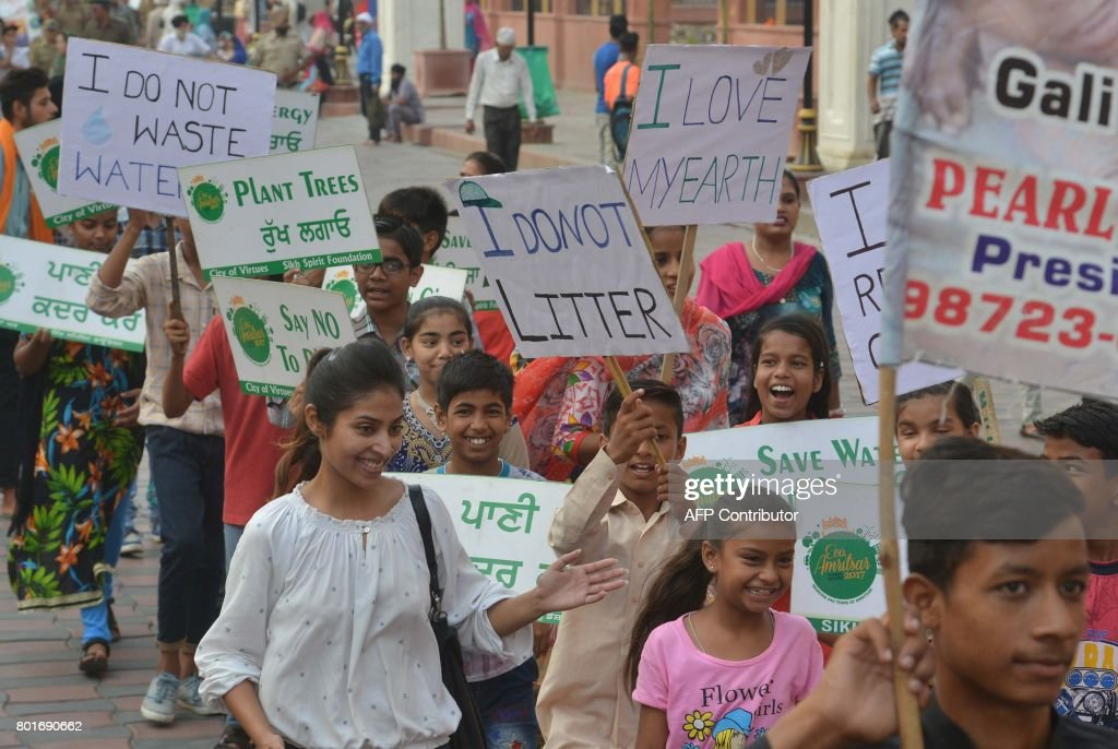 Indian students hold placards during an environmental awareness march held to mark the 440th Foundation Day in Amritsar on June 27 2017 Amritsar one..