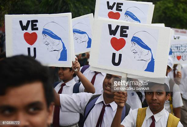 Indian students hold posters and placards as they prepare to take part in a walk alongside Roman Catholic nuns from the Missionaries of Charity to...