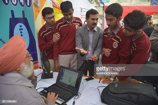 Indian students listen to an Unique Identification Authority of India officer Anil Bhatia as he withdraws money from his bank account with an Aadhaar...