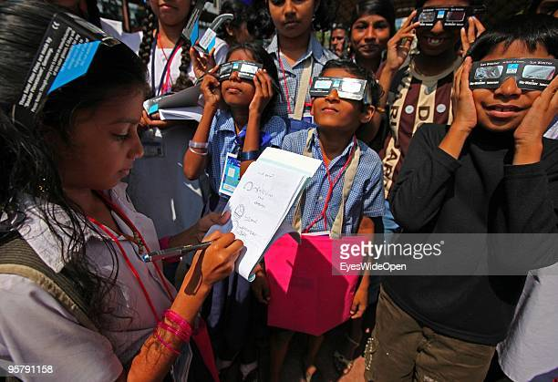 Indian students observe the rare Annular Solar Eclipse while one girl is drawing the process at the central stadium on January 15 2010 in...