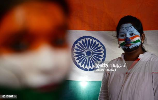 Indian students pose with their faces painted with the Indian national flag at an event during Indian Independence Day celebrations in Chennai on...