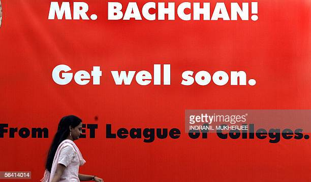 Indian students walk past a hoarding put up for Bollywood movie legend Amitabh Bachchan outside a city hospital where he is recuperating from bowel...