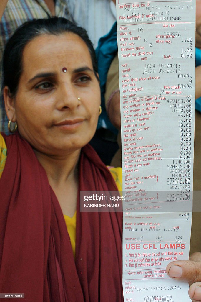 Indian Sudesh Kumari poses with an electricity bill for 573640 rupees for two months worth of power consumption for her residence of three people in..