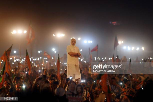 TOPSHOT Indian supporter listens as Indian Prime Minister Narendra Modi delivers a speech during a rally ahead of Phase VI of India's general...