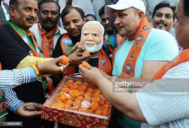Indian supporters and Bharatiya Janata Party workers offer sweets to another wearing a mask of the newly sworn-in Indian Prime Minister Narendra Modi...