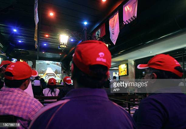 Indian supporters from the Formula One Pebble Street fan club watch the opening of the Indian Formula One Grand Prix at a bar in New Delhi on October...