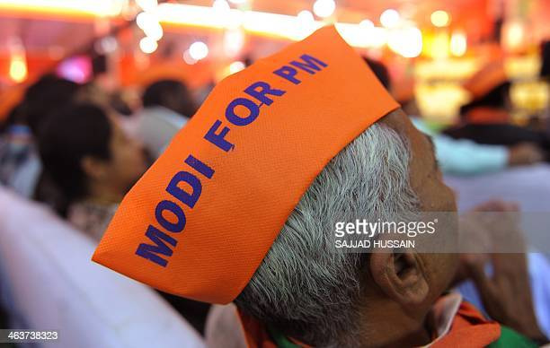 Indian supporters listen to a speech of Bharatiya Janata Party prime ministerial candidate and Gujarat state Chief Minister Narendra Modi during the...
