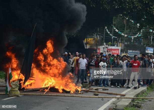 Indian supporters of a separate Gorkhaland state stand by a blazing road block during clashes with police in Sukna village in Darjeeling district on...
