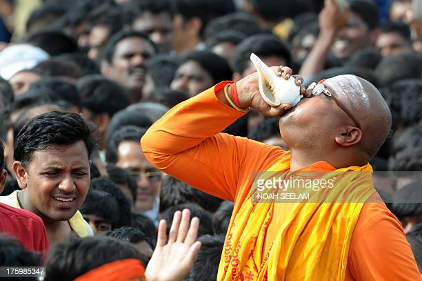 Indian supporters of Bharatiya Janata Party blow a Shankham as Chief Minister of Gujarat state and national election campaign chief of the main...