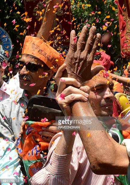Indian supporters of Bharatiya Janata Party celebrate their party victory in front of the BJP headquarters in New Delhi on May 16 2014 India's...