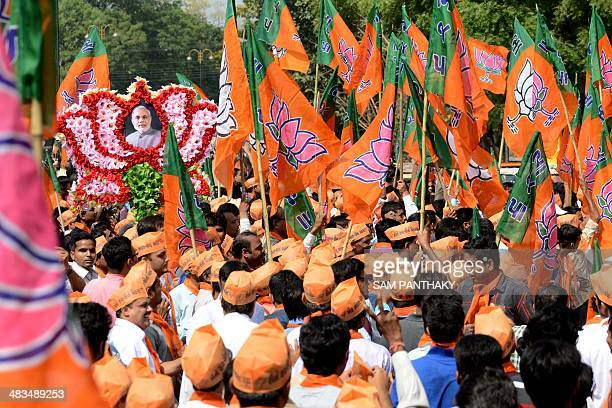 Indian supporters of Gujarat state Chief Minister and Bhartiya Janta Party 's prime ministerial candidate Narendra Modi carry a lotus with Modi's...