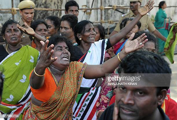 Indian supporters of Tamil Nadu Chief Minister Jayalalithaa Jayaram react as they wait to catch a glimpse of her funeral procession in Chennai on...