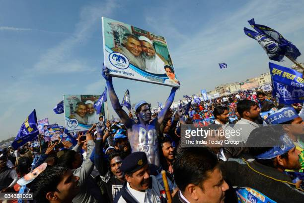Indian supporters of the Bahujan Samaj Party listen as Mayawati speaks during a election rally in Ghaziabad