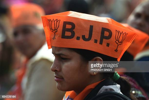 Indian supporters of the Bharatiya Janata Party listen to BJP Leader and Indian Prime Minister Narendra Modi as he speaks during a state assembly...
