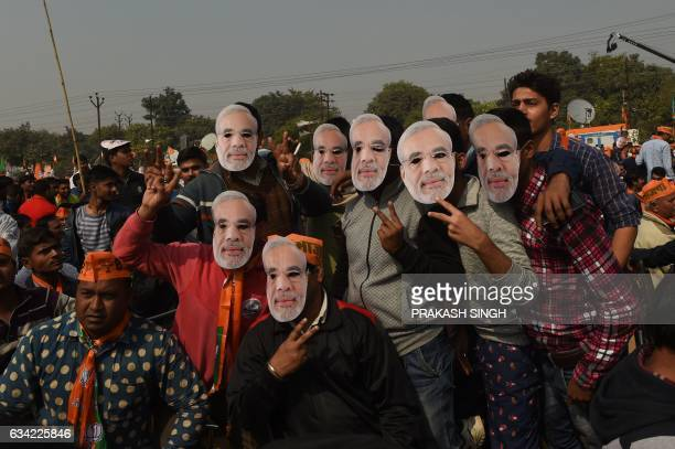 Indian supporters of the Bharatiya Janata Party pose with a mask with an image of Indian Prime Minister Narendra Modi at a state assembly election...