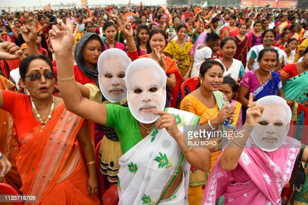 Indian supporters of the Bharatiya Janata Party shout slogans as they wear the mask of Prime Minister Narendra Modi during one of his political...