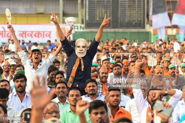 Indian supporters of the Bharatiya Janata Party shout slogans as they attend a metting of Prime Minister Narendra Modi political campaign ahead of...