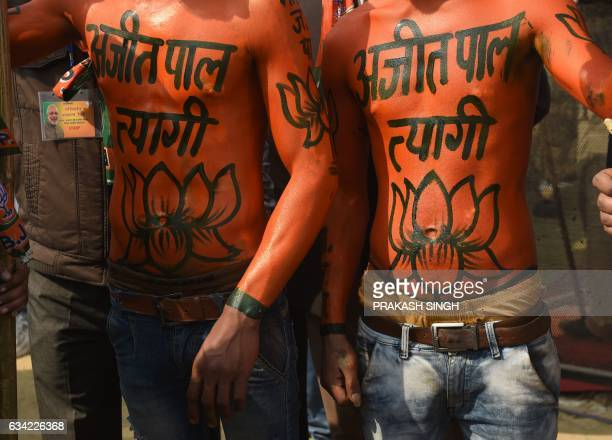 Indian supporters of the Bharatiya Janata Party their bodies painted with the BJP symbol cheer during an election rally adddressed by Indian Prime...