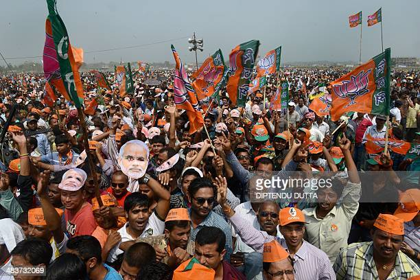 Indian supporters of the Bharatiya Janata Party wear masks of Chief Minister of the western Gujarat state and BJP Prime Ministerial candidate...