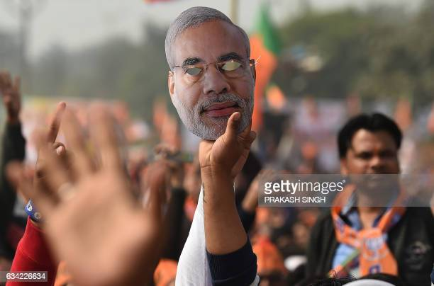 Indian supporters of the Bhartiya Janata Party listen to BJP Leader and Indian Prime Minister Narendra Modi as he speaks during a state assembly...