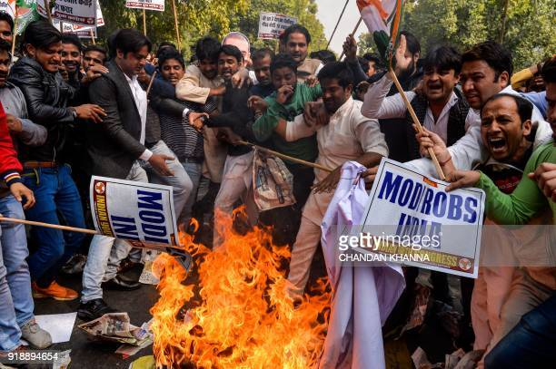 Indian supporters of the Congress Party shout slogans as they burn effigy of billionaire jeweller Nirav Modi in New Delhi on February 16 2018 Indian...