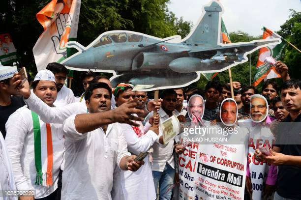 Indian supporters of the opposition Indian National Congress party hold a model of a Rafale fighter jet as they shouts slogans during a protest...