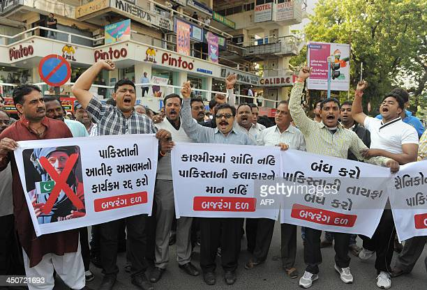 Indian supporters of the Vishwa Hindu Parishad and the Ahmedabad Bajrangdal shout slogans while holding banners showing the image of Pakistani singer...